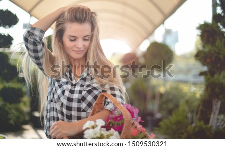 Happy customer in garden center holding basket with flowers