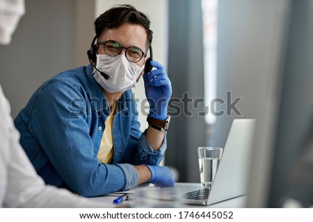 Happy customer service representative wearing protective face mask while working at call center and looking at the camera.