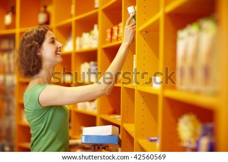 Happy customer taking medicine from a shelf