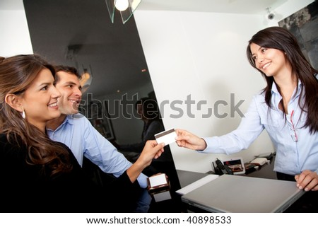 Happy custumers paying at the hotel with a credit card