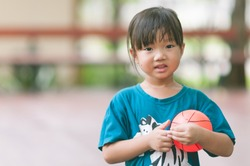 Happy cute asian girl smiling and  holding small basketball in the park with sun light background. Funny adorable Asia child playing mini ball alone in the garden with blurred background.