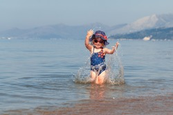 Happy cute baby girl in hat and sunglasses, swimming in sea