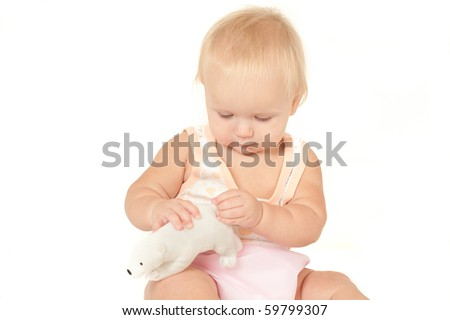 Happy cute baby girl (10 months) sitting on bed and playing with polar bear soft toy