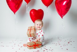 Happy cute baby kid toddler in pajamas sits on the floor with heart-shaped confetti, holds presents and shows his tongue. Red balloons on the background. St. Valentine's Day concept.