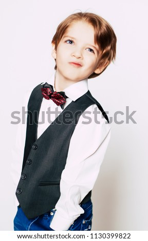 45b91b27a2e6 Happy cute blonde boy in suit and bow tie posing on white background and  smiling.