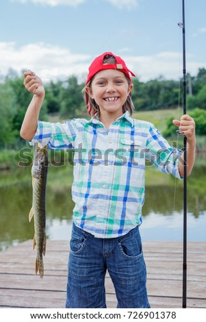 Happy cute boy enjoyed the fishing. Holding a big pike.
