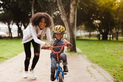 Happy cute boy learn to ride a bike with his mother. Mother teaching son to ride bicycle at park.