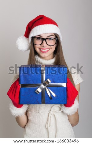 Happy cute Caucasian teenage girl with Santa hat holding a blue gift box wearing gloves and nerd glasses. Christmas and giving concepts.