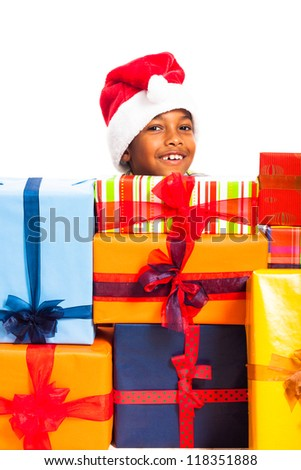 Happy cute child boy in Santa hat surrounded by colorful Christmas gift boxes, isolated on white background.