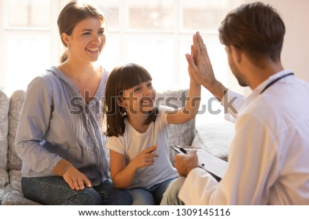 Happy cute child girl giving high five to male pediatrician welcoming little patient with mom at consultation, trusting kid and doctor celebrate good checkup medical results or getting cured healed