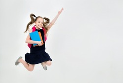 Happy cute child girl in school uniform holding books is jumping. Schoolgirl with facial expression isolated on white. Concept of education, reading, back to school.