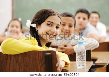 Happy cute children in classroom with their teacher
