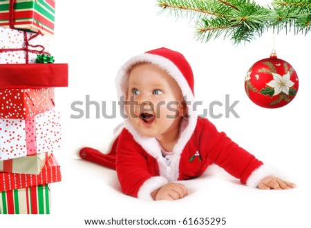 Happy, cute Christmas  baby under a tree branch with bauble and gifts isolated on white.