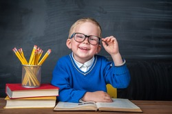 Happy cute clever boy is sitting at a desk in a glasses with raising hand. Child is ready to answer with a blackboard on a background. Ready for school. Back to school. Apple and books on desk