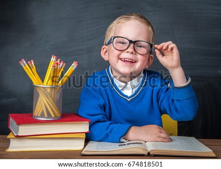 Happy cute clever boy is sitting at a desk in a glasses with raising hand. Child is ready to answer with blackboard ona background. Back to school. Apple and books on desk. First time to school #674818501