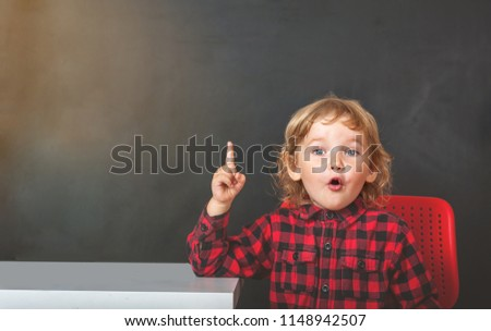 Happy cute clever kid is sitting at a desk and pointing up on blackboard. Child with toys for preschool and kindergarten. Children at home or daycare. Preschool girl in glasses. Early education.