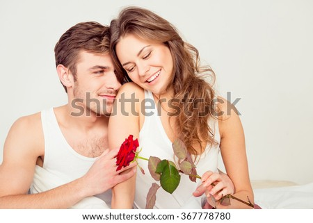 Happy cute couple in love at home embracing each other with a rose #367778780