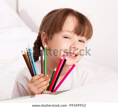 happy cute five year old girl sitting by the table and  drawing with pencils  at home