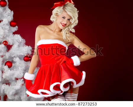 Happy cute girl in santa claus suit over red background