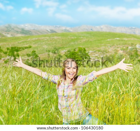 Happy cute girl on wheat field, smiling young lady enjoy open air, beautiful woman raised up hands, pretty teen playing outdoors, attractive female having fun outside, active life and freedom concept