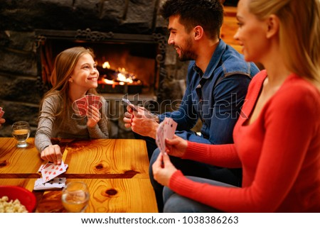 Happy cute girl playing card game with parents