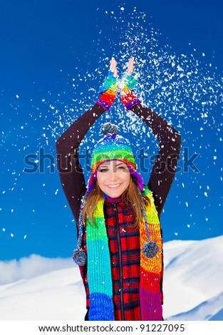 Happy cute girl playing with snow outdoor, throwing it up with hands, beautiful woman smiling with raised arms to blue sky and nature, young teen female in colorful hat, Christmas winter holidays
