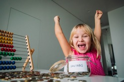 happy cute girl saving money, kid counting coins