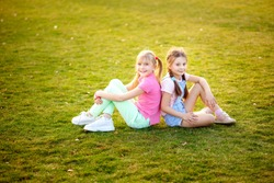 Happy cute girls sit on the grass by the children in the park