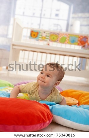 Happy cute infant lying on playmat, trying to crawl.?