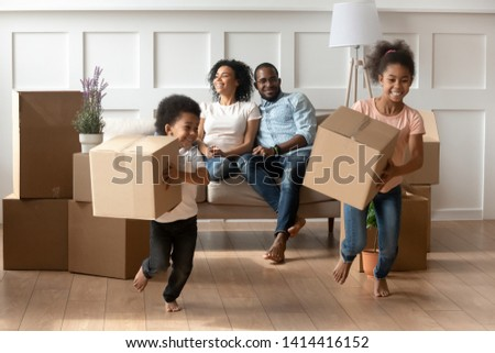 Happy cute little african kids holding boxes run play in living room while parents relax on moving day, black family renters tenants with children celebrate buy new home having fun renovate house stock photo