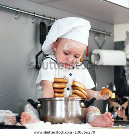 happy cute little baby in a cook cap with a pan