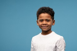 Happy cute little boy of African ethnicity in white t-shirt standing in front of camera against blue background in isolation