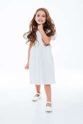 Happy cute little girl in dress smiling and walking over white background