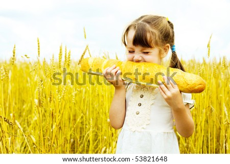 happy cute little girl in the wheat field eating a long loaf - stock photo