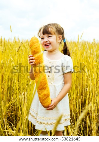 happy cute little girl in the wheat field with a long loaf