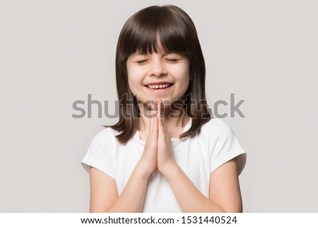 Happy cute little girl isolated on grey studio background keep hands in prayer hope believe ask good luck, hopeful smiling small child believer pray do religious superstitious gesture, faith concept #1531440524
