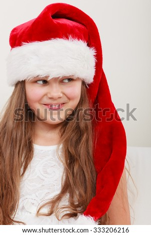 615d341dec45f Happy cute little girl kid in red santa claus hat and white dress.  Chrtistmas holiday