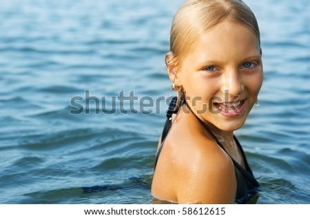 Happy Cute little girl swimming in water
