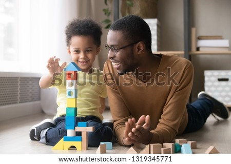 Happy cute little son playing game with black dad baby sitter building constructor tower from multicolored wooden blocks, african family father and toddler child boy having fun on warm floor at home