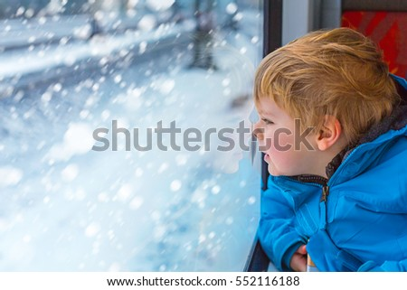 Happy cute little toddler boy looking out through window of a train, while it moving. funny adorable kid traveling and making winter family vacation. Travel concept, child having fun on railroad.