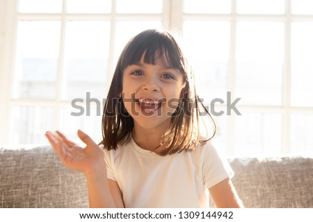 Happy cute little vlogger waving hand saying hello hi looking at camera talking to webcam, smiling kid child girl making online video call recording vlog sitting on sofa at home, portrait