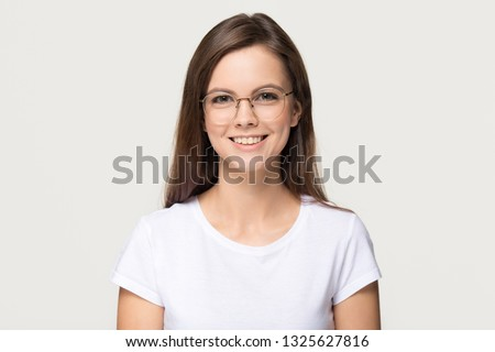 Happy cute millennial teen girl student in optical glasses looking at camera, smiling pretty young woman model in eyewear posing isolated on grey white blank studio background, head shot portrait