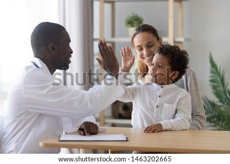 Happy cute mixed race child boy give high five to african man pediatrician welcome little patient and mom at consultation, trusting kid with doctor celebrate good medical health care treatment result