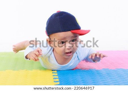 Happy cute 5 month old Asian baby boy with short black hair on rubber floor