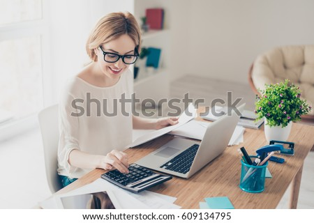 Happy cute  pretty accountant working with computer and calculator.