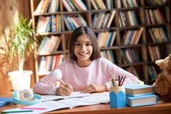 Happy cute smart hispanic indian preteen kid girl student, latin child primary school pupil studying at table at home, learning sitting at classroom desk looking at camera, schoolgirl portrait.
