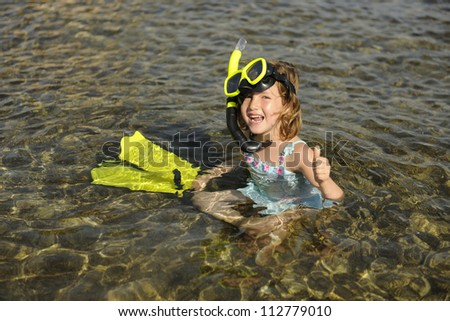 Happy cute snorkel girl on vacation in the water