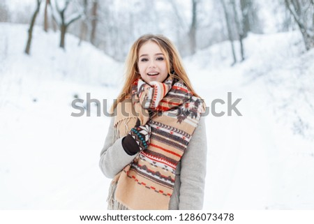 Happy cute stylish young woman in a vintage gray coat with fashionable wool warm scarf in mittens is walking in a snowy forest. Cheerful cheerful girl enjoys winter nature. #1286073478