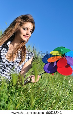 happy cute teen girl having fun with windmill in the field