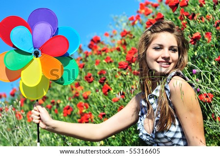 happy cute teen girl having fun with windmill on the poppy field